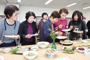 白あえやかんころ煮しめなどずらりと並んだお袋の味からお気に入りの料理を選ぶ参加者=武雄市のJAさがみどり武雄支所
