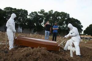 6日、ブラジル・リオデジャネイロで、新型コロナ感染症で死亡した父を埋葬する兄弟(ロイター=共同)