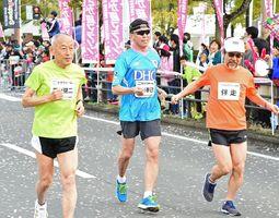 並んでスタートするゲストランナーの君原健二さん(左)と栁川春己さん(中央)。右は伴走者の渡邉啓一さん=県総合運動場陸上競技場前