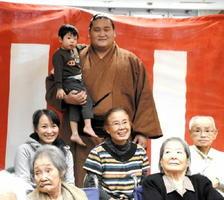 照ノ富士関と記念撮影する施設利用者とその家族ら=佐賀市兵庫町の介護老人保健施設「みどりの園」