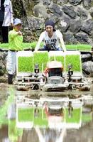 中川内稔さんに指導を受けて歩行用田植え機で作業する「ケイタク」の内山敬太さん=鹿島市三河内