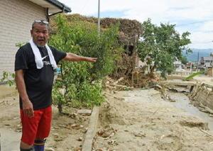 九州北部豪雨で、自宅のそばを流れる川が氾濫したときの様子を振り返った満生直樹さん=3日、福岡県朝倉市杷木
