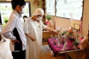 展示された作品を見る来場者ら=佐賀市多布施の「SUNSUNSUN飯屋」