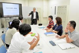 リーダー教員を養成するコースで、学校内外での連携や協働をテーマに議論する現職教員の院生(手前の6人)=10月上旬、佐賀市本庄町の佐賀大学教職大学院