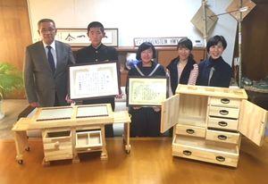 生徒作品コンクールの全国審査で2位になった大宅さん(左から2人目)と辻さん(同3人目)。使ってもらう家族と作品と一緒に市長に入賞を報告した=武雄市役所