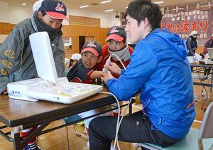 超音波検査で真剣に画面をのぞきこむ参加者=神埼市の神埼中央公園体育館