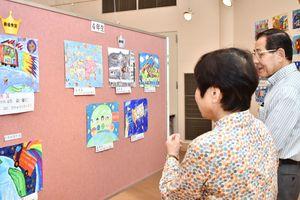 孫の作品を見に来て、他の作品にも感心するご夫婦=佐賀市の佐賀新聞社ギャラリー