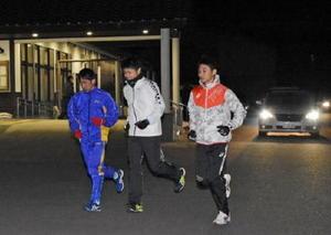 地区体育委員の車のライトに照らされ、ロード練習に向かう大川町体協の選手=伊万里市大川町