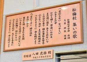 体育館に掲げられた「集いの歌」の銅板=佐賀市の小中一貫校松梅校