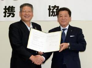 地域経済の活性化に向け、協定を交わした佐賀東信用組合の芹田泉理事長(右)と神埼市の松本茂幸市長=神埼市役所
