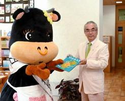一日図書館長を務めるいまりんモーモちゃんに寄贈する絵本を手渡す松永一広さん=伊万里市民図書館