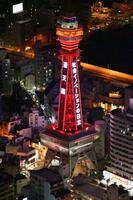 「大阪モデル」の警戒度を「赤信号」に引き上げることが決まり、赤色にライトアップされた通天閣=3日午後8時3分(共同通信社ヘリから)