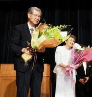 回顧録の出版記念祝賀会で花束を受け取る保利耕輔氏(左)と妻の美萌さん=唐津市の唐津シーサイドホテル