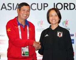記者会見でベトナムのチュン監督(左)と握手するサッカー女子日本代表の高倉監督=6日、アンマン(共同)