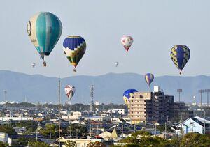 佐賀インターナショナルバルーンフェスタの代替イベントとして市街地を低空飛行するバルーン=31日朝、佐賀市(撮影・米倉義房)