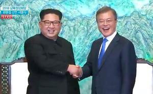 板門店宣言に署名し、握手する北朝鮮の金正恩朝鮮労働党委員長(左)と韓国の文在寅大統領=27日、板門店の韓国側施設「平和の家」(板門店共同映像取材団・共同)