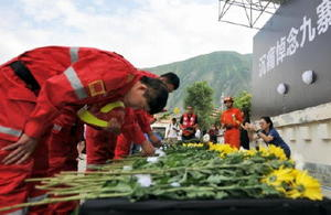地震の被害が出た九寨溝県で開かれた追悼式典で、献花する救助関係者=15日、中国四川省アバ・チベット族チャン族自治州