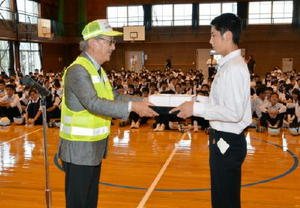 生徒代表に反射材を贈る三日月町駐在所等連絡協議会の江口尚久会長(左)=小城市の三日月中学校