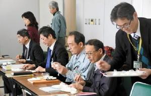 他地域のブランド米と東与賀町産の特別栽培米「夢しずく」を試食する会議参加者=佐賀市東与賀支所