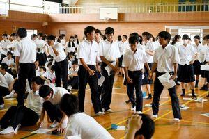選挙に関するクイズで、悩みながら解答に移動する生徒=小城高