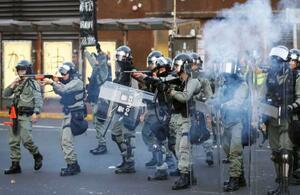 香港・新界地区の商業施設付近で若者らに向け催涙弾を放つ警察官ら=22日、香港(共同)