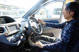 身体障害者向けの改造車両を操作してみせる江下真也さん。「この取り組みをモデルケースにできれば」と意気込む=佐賀市北川副町のオートガレージ江下