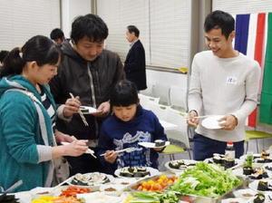 対面式で留学生が手作りした日本料理を通して交流する参加者=佐賀市白山の県国際交流プラザ