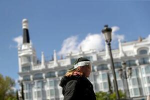 手作りしたシールド状の透明なマスクをつけてマドリード市内を歩く女性=4日(ロイター=共同)