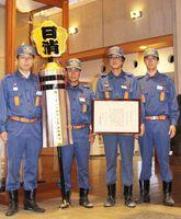まといを手にする相知支団長の梶山義人さん(左から2人目)と団員