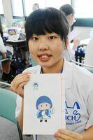 できあがった和綴じ本を手にする生徒=伊万里市民会館