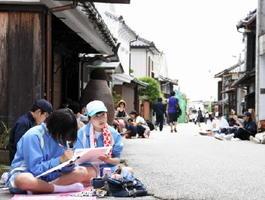 真剣な表情で伝統的な町並みを描く参加者たち=鹿島市浜町の酒蔵通り