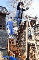 田んぼに水をくみ上げるため、生産者の原口義実さん(左)と一緒に二連水車をこぐ児童=佐賀市東与賀町