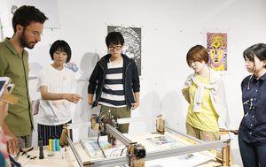 自作した機械を動かして、参加者に紹介するグラフィックデザイナーのギルス・ドゥ・ブロックさん(左)=佐賀市のオランダハウス