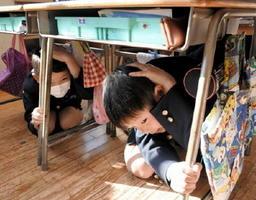 落下物から身を守る訓練で、机の下に潜り込み、手で頭を守る児童たち=佐賀市の本庄小学校