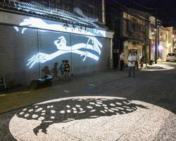 鳥取県境港市の「水木しげるロード」で始まった「動く妖怪影絵」=1日夜