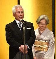 旭日小綬章受章祝賀会で謝辞を述べる江口敏文さん。右は妻の妃佐子さん=佐賀市のホテルニューオータニ佐賀