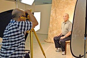 りんとした表情の男性(右)をカメラに収める木下智博さん=佐賀市の佐賀玉屋
