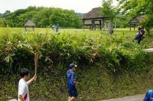 御所野遺跡(奥)の近くを通過する聖火ランナー(左手前)=16日午後、岩手県一戸町