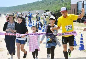 家族と手を取り、一緒にゴールテープを切る唐津市の藤田昇吉選手(右)=唐津市の東の浜
