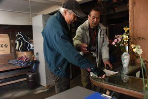 屋内を調べ、間取りを書く坂井さん(左)=佐賀市大和町の古民家
