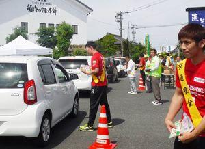 啓発チラシを手に交通安全を呼び掛けるレッドトルネードの選手ら=神埼市神埼町横武(提供写真)