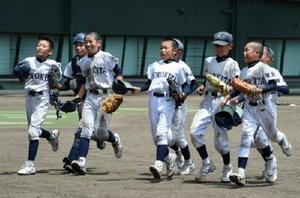 優勝を決め、笑顔でベンチに駆け寄る諸富北小クナイン=佐賀市のみどりの森県営球場