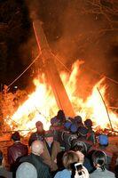 巨大なたいまつを綱で引っ張り、正月飾りを燃やす消防団員=7日夜、唐津市の唐津天満宮(撮影・山口源貴)
