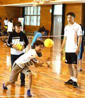 トヨタ紡織九州レッドトルネードの選手たちの前で、力強くボールを投げ込む子どもたち=神埼中央公園体育館