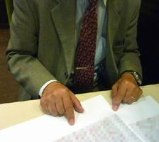 事業者によるマッサージなどの療養費の不正受給について、書類を示して証言する元社員の男性(画像の一部を加工しています)