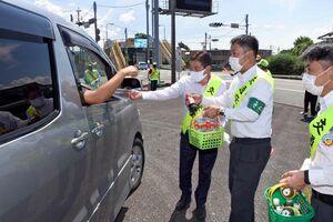 国道を通行するドライバーに飲み物などを配る参加者=鳥栖市田代本町の田代交番