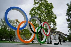 五輪マークのモニュメントと国立競技場(奥)。新型コロナウイルスの影響で延期となった東京五輪は14日で開幕まで100日となった=13日午後、東京都新宿区
