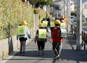 修了式のため登校する小学校の児童=24日午前、東京都葛飾区