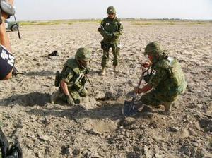 2004年8月、イラク・サマワ宿営地付近の着弾地点を調べる陸上自衛隊員(防衛庁陸上幕僚監部提供)