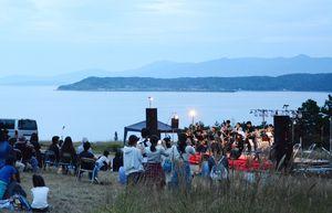 海を臨むロケーションの中、音楽に耳を傾ける来場者=唐津市屋形石の七ツ釜